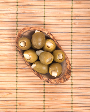 Green colossal olives hand stuffed with garlic gloves in olive wood bowl isolated on bamboo placemat