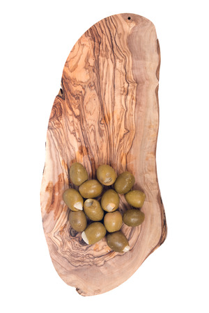 Green colossal olives hand stuffed with garlic gloves in olive wood cutting board isolated on white background Фото со стока