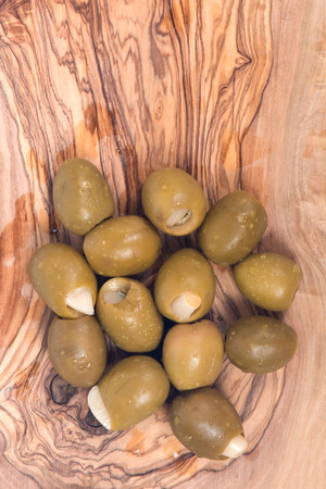 Green colossal olives hand stuffed with garlic gloves in olive wood cutting board