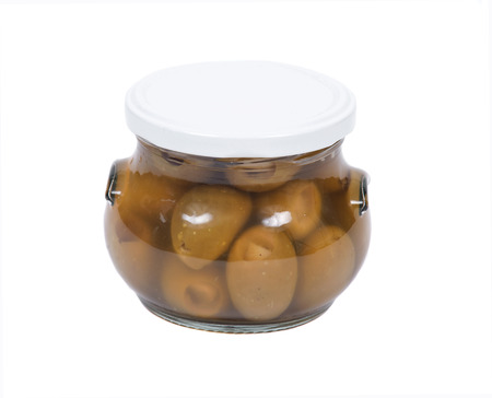Green colossal olives hand stuffed with garlic gloves in jar isolated on white background Фото со стока