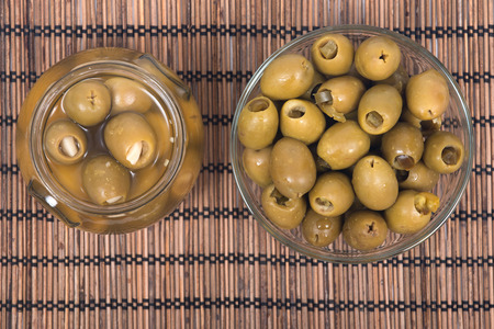 Green colossal olives hand stuffed with jalapeno peppers and garlic gloves in bowl on bamboo placemat Фото со стока