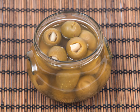 Green colossal olives hand stuffed with garlic gloves in jar on bamboo placemat
