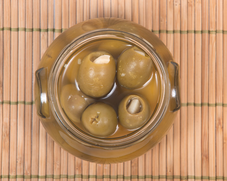 Green colossal olives hand stuffed with garlic gloves in jar om bamboo placemat