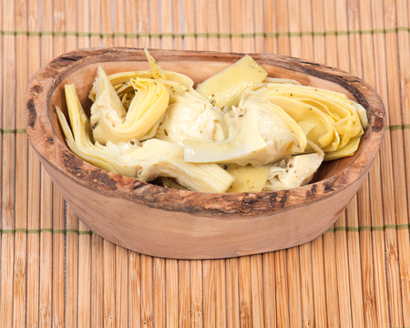 ascorbic acid: Food of love, marinated artichokes in olive wood bowl on bamboo placemat Stock Photo