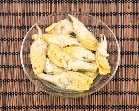 ascorbic acid: Food of love, marinated artichokes in bowl on bamboo placemat