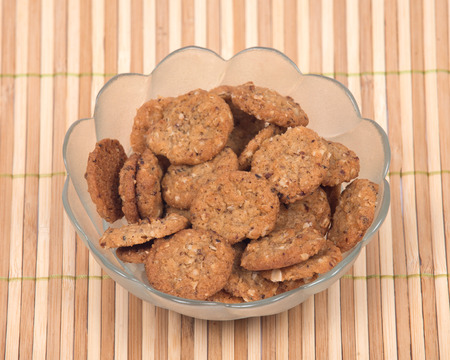 Crispy crunchy oatmeal raisin cookies in bowl on bamboo placemat Stock Photo