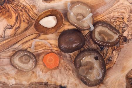 ascorbic acid: Shiitake marinated mushrooms with wooden spoon on olive wood cutting board