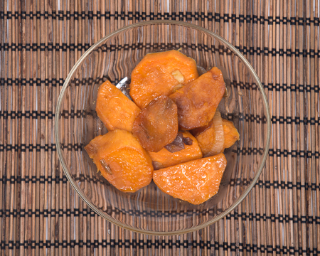 Roasted sweet potatoes with red onion in clear glass dish on bamboo placemat
