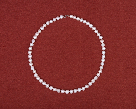freshwater: Freshwater pearl necklace on red fabric background Stock Photo