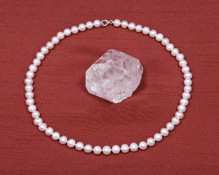 freshwater pearl: Freshwater white pearl necklace and crystal quartz gemstone on red fabric background