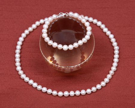 freshwater pearl: Freshwater white pearl necklace and crystal ball on red fabric background