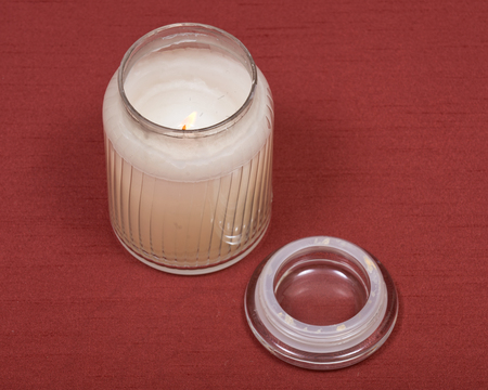 Burning white candle in glass jar on red fabric background