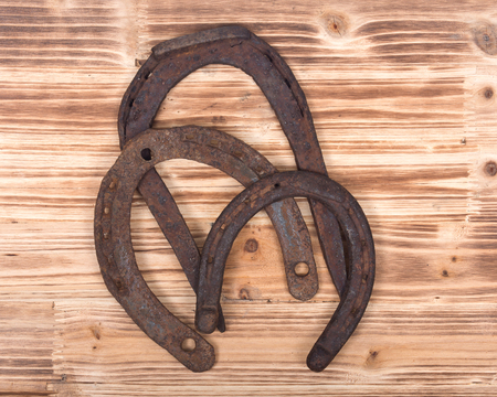 Old rusty vintage good luck horseshoe on wooden tray like background Stock Photo