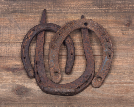 lucky charm: Old rusty vintage good luck horseshoe on wooden tray like background Stock Photo