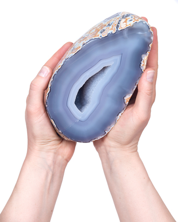 Young woman holding partially polished blue lace agate geode with crystaline druzy center isolated on white background