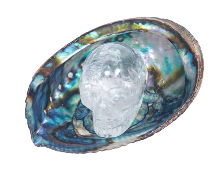 spiritual energy: Clear quartz skull in bright polished rainbow abalone shell isolated on white background Stock Photo
