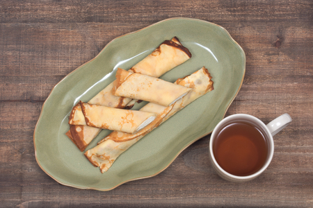 Delicious cheese blintz on green plate and cup of tea on wooden vintage tray 写真素材