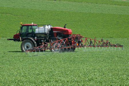 Tractor with agricultural sprayer machine for pesticide spraying Stock Photo
