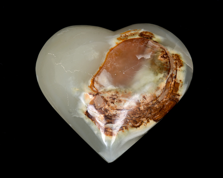 Polished multicolor carved onyx heart on black background