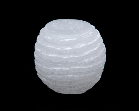 White selenite carved tea light holder on black background Stock Photo