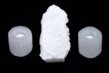 White mexican fish tail selenite and selenite cylinder tea light holder on black background