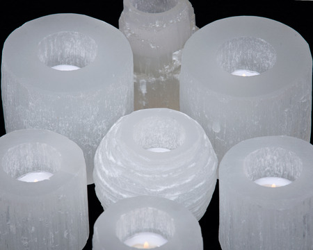 White selenite tea light holders on black background