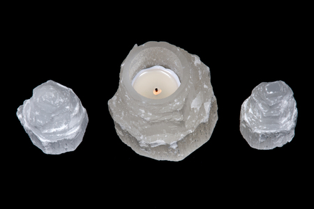 White selenite cylinder tea light holder on black background