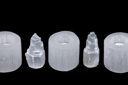 White selenite cylinder tea light holders and everest carving on black background Stock Photo