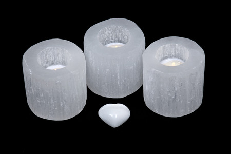 White selenite cylinder tea light holders and heart on black background Stock Photo