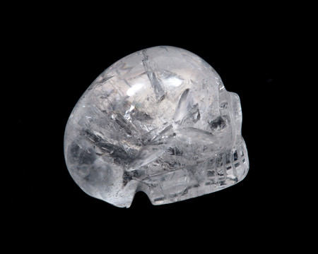 Clear quartz skull with rainbow on black background Stock Photo