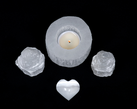 White selenite cylinder tea light holder, heart and everest carving on black background