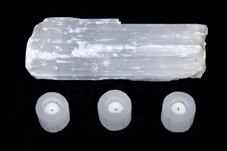 Natural decorative selenite log and selenite cylinder tea light holders on black fabric background Stock Photo