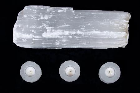 chakra energy: Natural decorative selenite log and selenite cylinder tea light holders on black fabric background Stock Photo