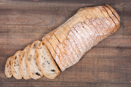 Sliced crusty ciabatta organic italian bread on wooden vintage tray
