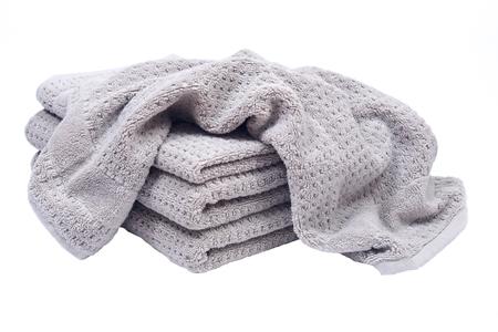 Stapel, voorraad dikke organische katoenen badhanddoeken die op witte achtergrond worden geïsoleerd