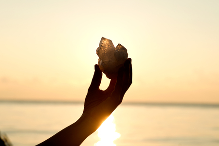 reiki: Young womans hands holding clear quartz point in front of the lake sunrise