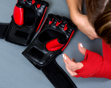 Young active woman getting prepared for exercises wrapping her hands with red bandage tape in homemade gym, fitness
