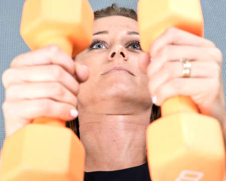 Active young woman using a orange dumbbell for her arm exercise in homemade fitness gym studio