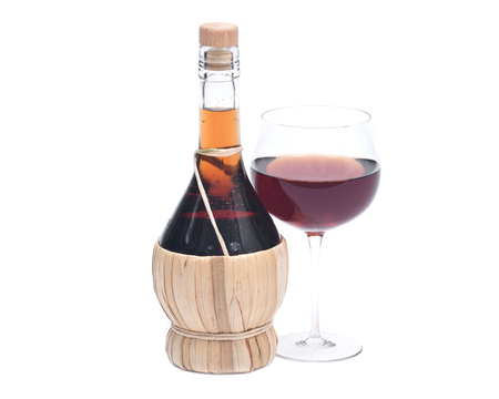 shabbat: Red pomegranate wine in glass and straw wine bottle isolated on white background Stock Photo