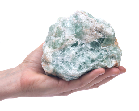 Womans hand holding Green Apophyllite Cluster in matrix isolated on white background