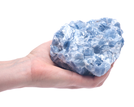striated: Womans hand holding raw blue calcite cluster isolated on white background