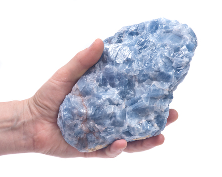 Womans hand holding raw blue calcite cluster isolated on white background