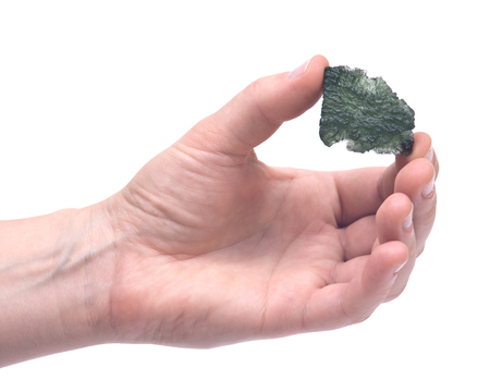 Womans hand holding Moldavite (form of tektite found along the banks of the river Moldau in Czech republic) isolated on white background Stock Photo