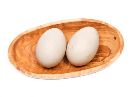 Unwashed fresh organic gmo and soy free pasture raised chicken eggs in wooden bowl isolated on white background