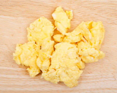 Organic duck scrambled eggs on wooden cutting board Stock Photo