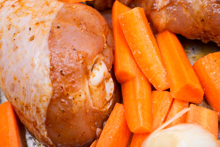 Marinated chicken, carrots, onion and garlic in metallic roaster oven pan