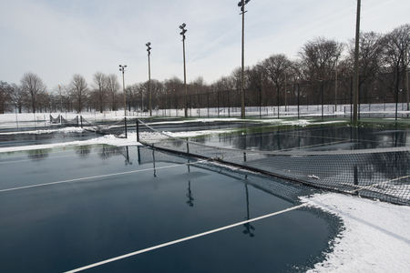 Public hard tennis court covered with snow and water waiting for spring