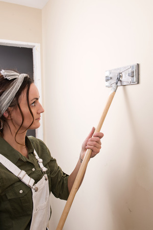 Young woman is sanding wall with pole sander before painting in house under remodeling Banco de Imagens