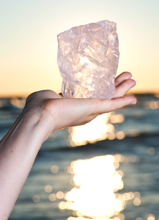 Womans hand holding gem grade rough Rose Quartz chunk from Madagascar  in front of the lake at sunrise Stock Photo