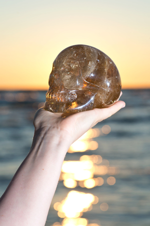 Woman's hand holding big  natural Citrine  Quartz skull at the sunrise in front of the lake.